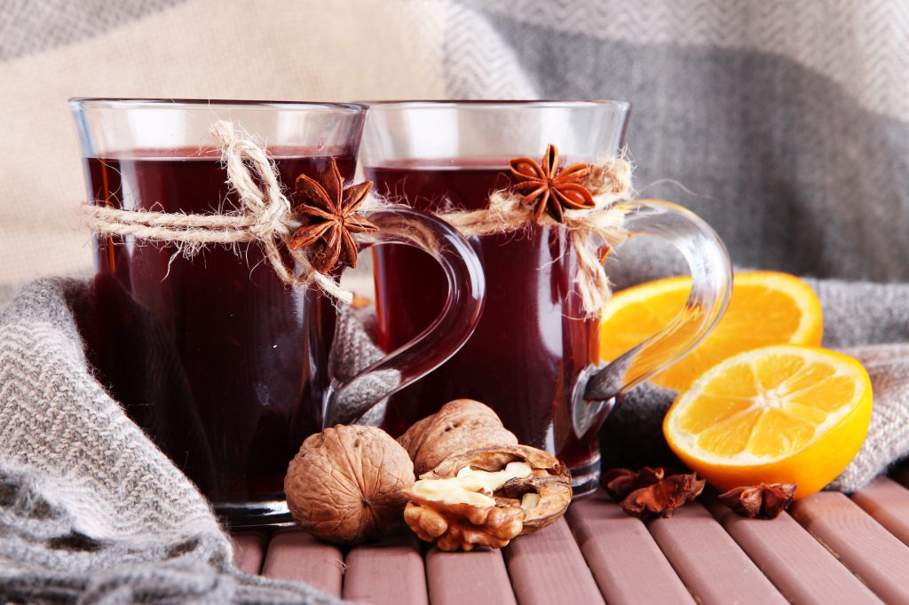 Mulled wine with orange and nuts on table on fabric background